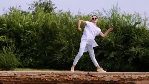 Moderní žena baletku. Mladá sportovní tmavě ženy tančí nahoře červená cihlová zeď na ulici. 4k