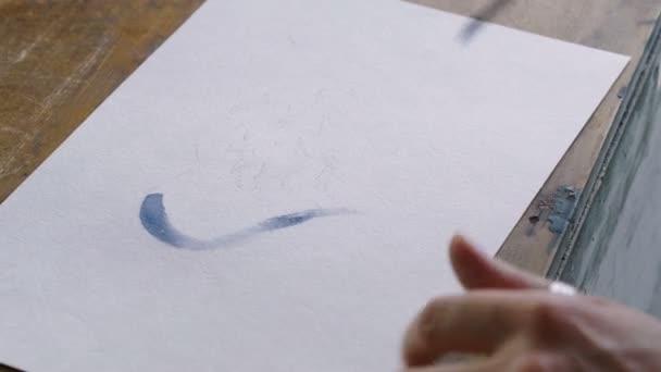 Detailní záběr rukou umělců žena Malování modré srdce v akvarely pomocí štětcem v ateliéru. 4k
