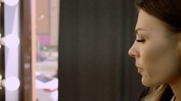 Profil mladé docela tmavé ženy použití očních stínů na víčka pomocí štětce na make-up. 4k