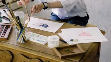 The hands of woman artist painting pictures in watercolors on sheet of paper using a paintbrush in the art studio. 4K