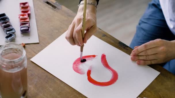 Close-up shot of the female artists hands painting a red heart in watercolors using a paintbrush in the art studio. 4K