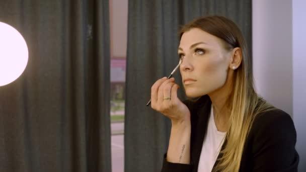 Kinderschminken. junge schöne dunkle Frau schminkt sich im Studio. 4k