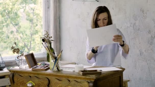 The woman artist painting picture in watercolors on sheet of paper using a paintbrush in the art studio. 4K