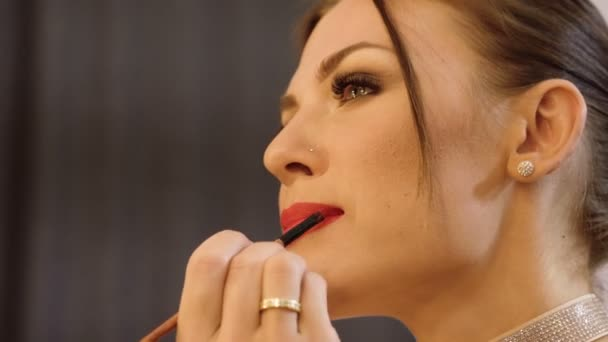 Face make-up. Close-up shot of young brown-haired woman applying a red lipstick on her lips. 4K