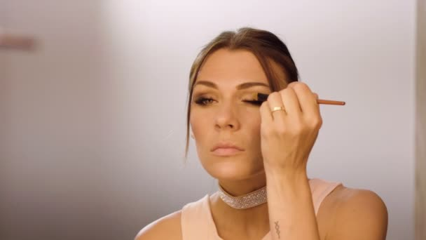 Face make-up. Portrait a young beautiful woman applying smoky eyeshadow on the eyelids. 4K