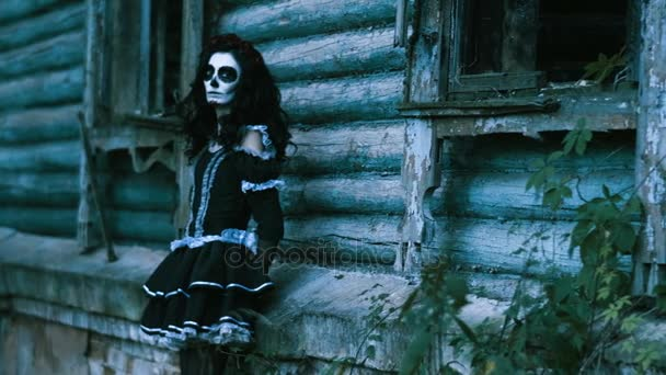 Der mexikanische Tag der Toten. Die junge Frau mit dem furchterregenden Make-up für Halloween steht in schwarzen Kleidern vor einer Holzwand. 4k