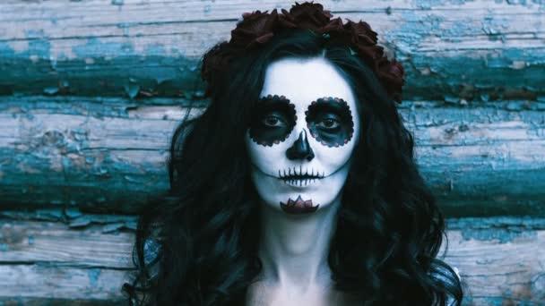 Die mexikanischen Tag der Toten. Das Porträt der jungen Frau mit erschreckenden Make-up für Halloween auf dem Hintergrund der Holzwand. 4k