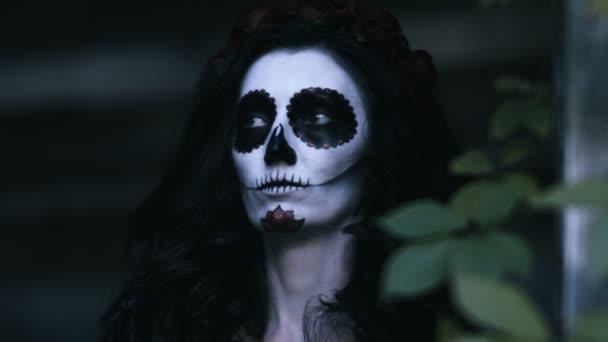 Die mexikanischen Tag der Toten. Die junge Frau mit gruselig Skelett Halloween Make-up hält einen Kürbis mit einer brennenden Kerze. 4k