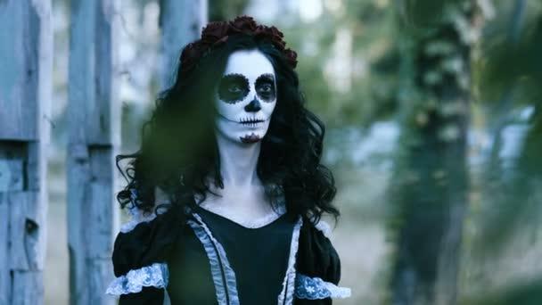 Die mexikanischen Tag der Toten. Das Porträt der jungen Frau mit erschreckenden Make-up für Halloween vor alten Holzhaus steht und schaut sich um. 4k