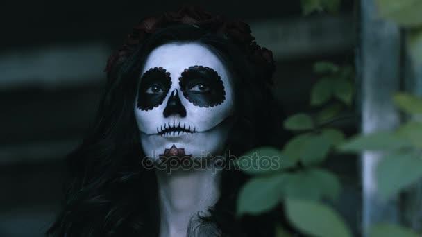 Der mexikanische Tag der Toten. Die junge Frau mit gruseliger Totenkopf-Halloween-Schminke hält einen Kürbis mit brennender Kerze in den Armen. 4k