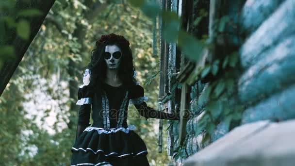 Der mexikanische Tag der Toten. die junge Frau mit dem beängstigend geschminkten Skelett für Halloween in schwarzen Kleidern durch das verlassene Holzhaus. 4k