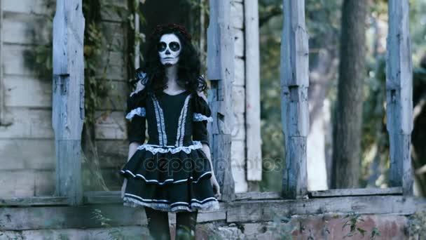 Die mexikanischen Tag der Toten. Die junge Frau mit unheimlich Make-up für Halloween verkleidet in schwarzer Kleidung vor verlassenes Holzhaus steht. 4k