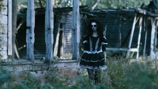 Die mexikanischen Tag der Toten. Die junge Frau mit unheimlich Make-up des Skeletts für Halloween verkleidet in schwarzer Kleidung geht entlang der verlassenen Holzhaus. 4k
