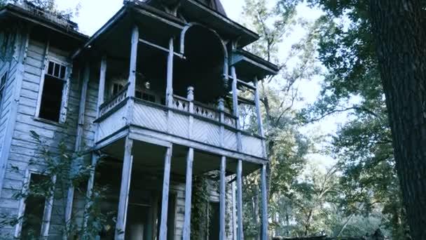 Die mexikanischen Tag der Toten. Die junge Frau mit unheimlich Make-up des Skeletts für Halloween verkleidet in schwarzer Kleidung geht entlang der verlassenen zweistöckiges Holzhaus. 4k