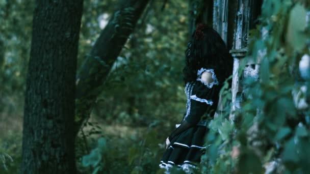 Der mexikanische Tag der Toten. die junge Frau mit gespenstischem Skelett-Make-up für Halloween in schwarzer Kleidung lehnt an einer Holzwand und blickt in die Kamera. 4k