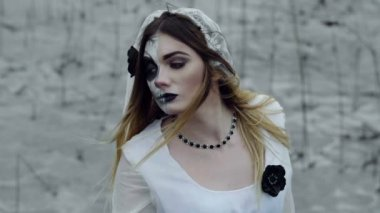 The young woman with frightening make-up of dead bride for Halloween dressed in a white wedding gown going through the field of dried grass. Slow motion. HD
