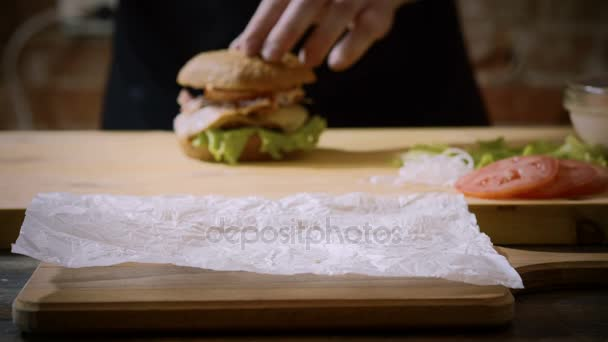 Vaření burger. Close-up shot kuchaři ruce dát lahodné připravené hamburger hovězí karbanátek na popředí. 4k