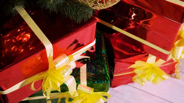 Close-up of four red and one green gift boxes under decorated Christmas tree. 4K