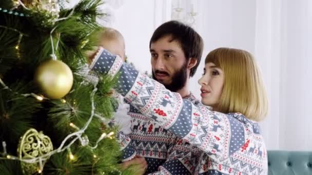 Family holiday. Mother, father and male child looking at Christmas tree. 4K