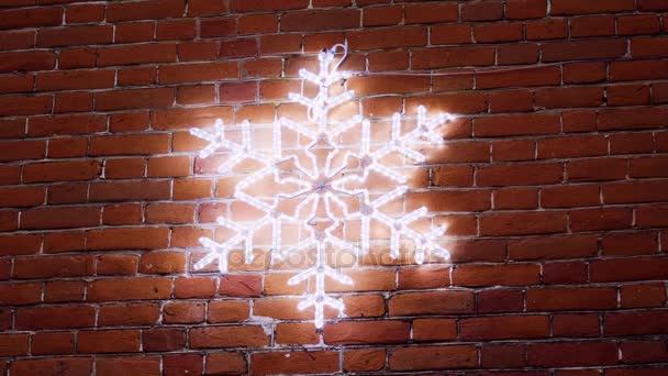 A Snowflake Made From Christmas Lights Hanging On The Wall Of A Brick House 4k