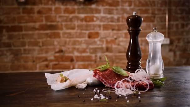 Masné výrobky. Šťavnaté maso hovězí steak na dřevěný stůl s sůl, černý pepř, nakrájenou cibuli. 4k