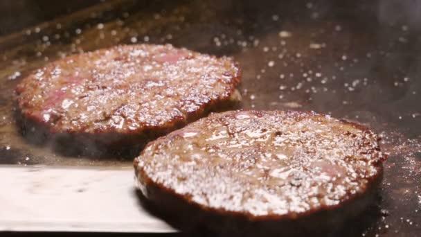 Detailní záběr dvou hovězí nebo vepřové kotlety smažení na grilu. Zpomalený pohyb. HD