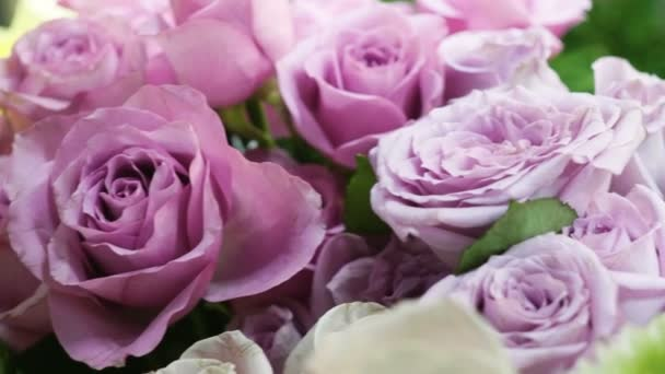 Close-up shot of a large bouquet of bright fresh lilac roses in a flower shop. 4K
