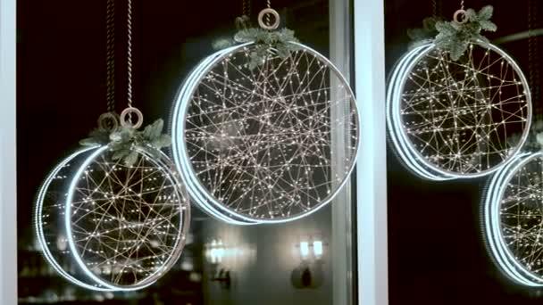 Obývací pokoj zařízený k Vánocům. Zářící girlandy visí v oknech. 4k