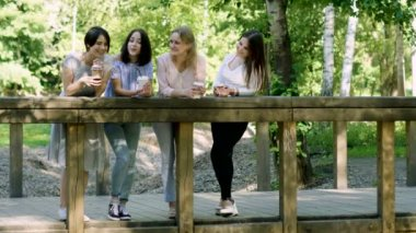 Four young pretty women walking in the park, talking and drinking beverages. 4K