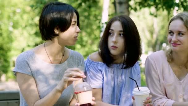 Négy fiatal csinos nők séta a parkban, beszélgetni, és ivott italok. 4k