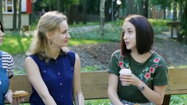 Tři krásné ženy jíst koláče a pití kávy sedí na lavičce venku. 4k