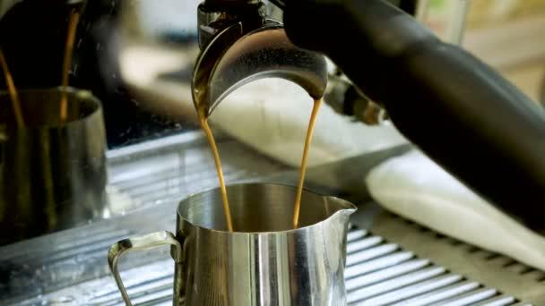 Forró italt. Közeli szemcsésedik-ból kávé gép szakadó espresso egy fém kancsóban. 4k