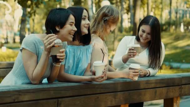 Čtyři mladé krásné ženy procházky v parku, mluví a pití nápojů. Zpomalený pohyb. HD