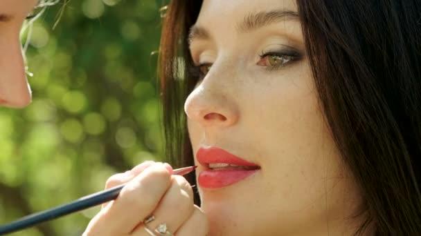 Kinderschminken. Nahaufnahme einer professionellen Visagistin, die mit einem Pinsel einen roten Lippenstift auf die Lippen von Frauen aufträgt. 4k