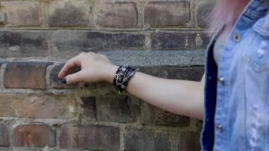 Womens hand with a black leather wristband moving along the brick wall. Slow motion. HD