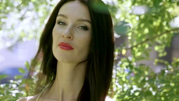 Csinos, fiatal nő, és mosolyogva néz a kamera portréja. Lassú mozgás. HD