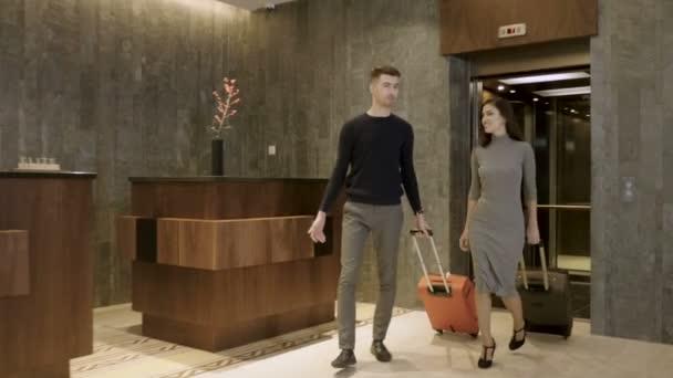 attraktives glückliches Paar, das im Hotel ankommt und vom Aufzug in die Empfangshalle geht, um einzuchecken. 4k