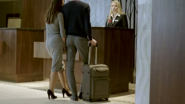 Šťastný mladý atraktivní muž a žena odbavení na recepci v luxusním hotelu. 4k