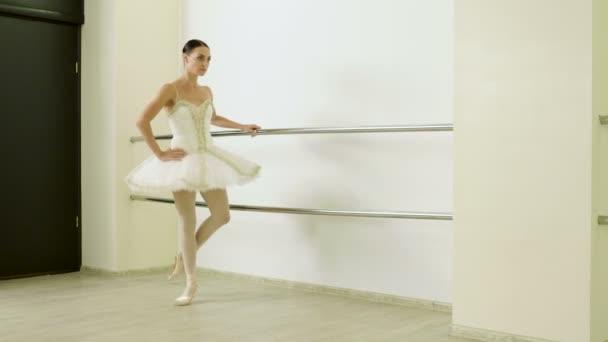 Classical ballet. Ballerina warming in pointe shoes in dance studio. 4K