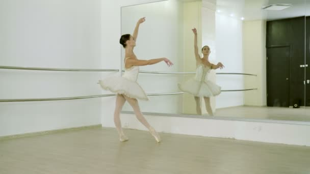 Classical ballet. Ballerina dancing in pointe shoes in dance studio with mirrors. 4K