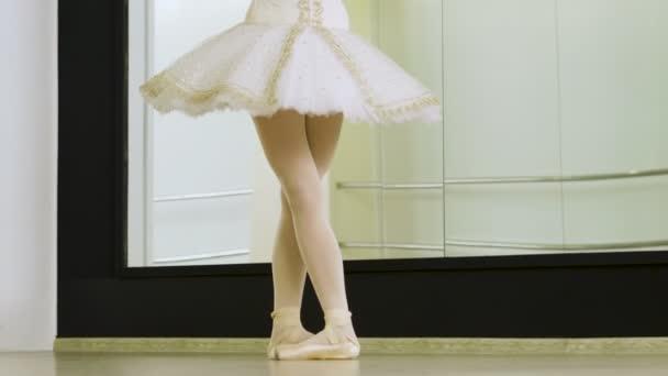 Close-up shot of feet of female ballet dancer dancing on tiptoe in pointe shoes in dance studio. 4K