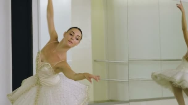 Young beautiful ballerina dressed in white tutu dancing gracefully on her pointe ballet shoes. 4K