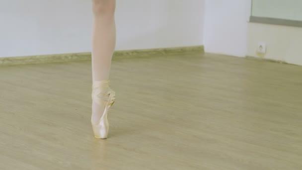 5ea47317c Toma primeros planos de pies de bailarina de ballet mujer bailando de  puntillas en los zapatos del pointe en estudio. 4k