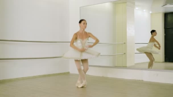 Dance of ballerina. Graceful female ballet dancer doing a workout in pointe shoes in the classroom. 4K