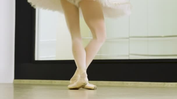 Close-up shot of feet of female ballet dancer dancing on tiptoe in pointe shoes in dance studio. 4K