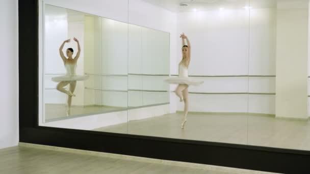 Dance of the ballerina. Female ballet dancer dancing in pointe shoes in studio. 4K