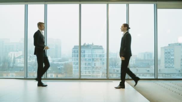 Dva podnikatelé v oboru vyhovuje navzájem pozdrav s handshake a diskutovat o práci před velkým oknem. 4k