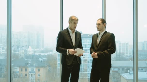 Two businessmen are talking, standing at the panoramic window and using a digital tablet. 4K