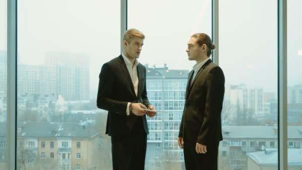 Zwei Geschäftsleute in Business-Anzügen stehen mit digitalem Tablet vor einem Panoramafenster mit Blick auf die Stadt. 4k