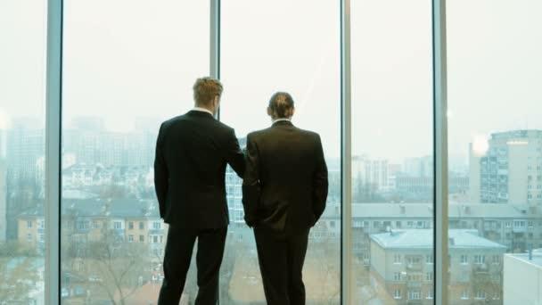 Pohled zezadu na dvou mužů v podnikání obleky, stojící před panoramatická okna s výhledem na město a povídali. 4k
